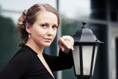 Beautiful fashion woman standing at lamppost — Stock Photo