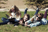 Teenage school girls lying on the grass in campus  — Foto Stock