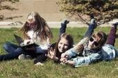 Teenage school girls lying on the grass in campus  — Stock Photo