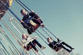Teenage girls on the chain swing carousel — Stock Photo