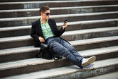 Young man with a mobile phone sitting on the steps — Stock Photo