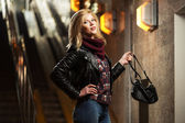 Young fashion blond woman in leather jacket with handbag — Stock Photo