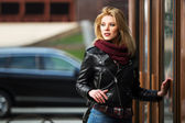 Young fashion blond woman in leather jacket at the mall door — Stock Photo