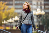 Young fashion blond woman walking on the city street — Stock Photo