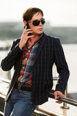 Young fashion man in sunglasses calling on mobile phone outdoor — Stock Photo