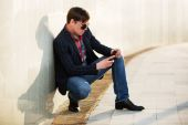 Young fashion man in sunglasses with a mobile phone at the wall — Stock Photo