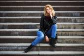 Young fashion blond woman in leather jacket sitting on the steps — Stock Photo