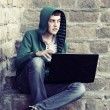 Young man with laptop sitting on the steps — Stock Photo #64187323