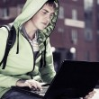 Young man with laptop sitting on the steps — Stock Photo #64187335