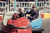 Happy teenage girls driving a bumper cars — Stock Photo