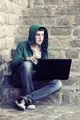 Young man with laptop sitting on the steps — Stock Photo