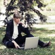 Fashion business woman using laptop in a city park — Stock Photo #64386231