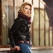 Young fashion blond woman in leather jacket at the mall window — Stock Photo #64386841
