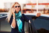 Fashion business woman calling on the phone at the car — Stock Photo