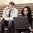 Young business couple with laptop on the steps — Stock Photo #66508481