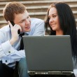 Young business couple with laptop on the steps — Stock Photo #66508491