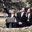 Young business people using laptop in a city park — Stock Photo #68523897