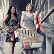 Two young fashion women with shopping cart in the mall — Stock Photo #71736297