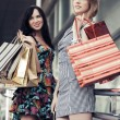 Two young fashion women with shopping bags in the mall — Stock Photo #71736307