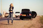 Fashion woman next to broken car calling on cell phone  — 图库照片
