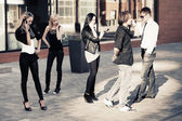 Group of young fashion men and women calling on mobile phones  — Stock Photo