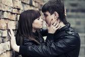 Gelukkige jonge paar verliefd op de bakstenen muur — Stockfoto