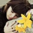 Sad young woman lying on the tombstone — Stock Photo #77788496