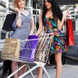 Two young fashion women with shopping cart in the mall — Stock Photo #77788600