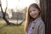 Smiling Little Girl Beside A Tree — Stock Photo