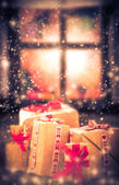 Christmas gifts rustic table window dark snowing — Stock Photo