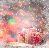 Winter background wrapped gifts wooden trunk snowing — Foto de Stock