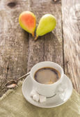 Coffee cup black wooden board brown pears white — Stockfoto