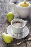 Coffee cup black wooden board brown pears white jug — Stock Photo