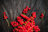 Red currant fruit scattered wooden bench table — Stock Photo