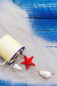 Colorful shells cup sand strewn blue boards — Stock Photo