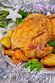 Chicken Christmas with vegetables and silver tinsel — Stock Photo