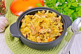 Cabbage stew with meat in black pot on napkin — Stock Photo