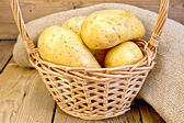 Potatoes yellow in basket with burlap on board — Foto Stock