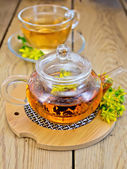 Herbal tea from tutsan in glass teapot on stand with cup — Stock Photo