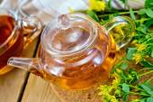 Herbal tea from tutsan in glass teapot with cup on board — Stock fotografie