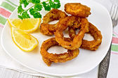 Calamari fried with lemon and fork on plate — Stock Photo