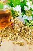 Tea from flowers of viburnum in strainer on board — Stockfoto