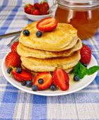 Flapjacks with strawberries and blueberries on blue tablecloth — ストック写真