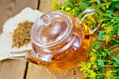 Tea with fresh and dry tutsan in glass teapo on board — Fotografia Stock