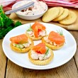Crackers with cream and salmon in plate on board — Stock Photo #57964213