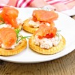 Crackers with cream and salmon on board — Stock Photo #57964245