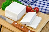 Feta with tomato and knife on wooden board — Stock Photo