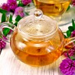 Tea with clover in glass teapot on light board — Stock Photo #58335675