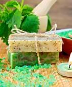 Soap homemade and candle with nettles in mortar on board — Stock Photo