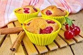 Cupcakes with cherries in tins on board — Stock Photo